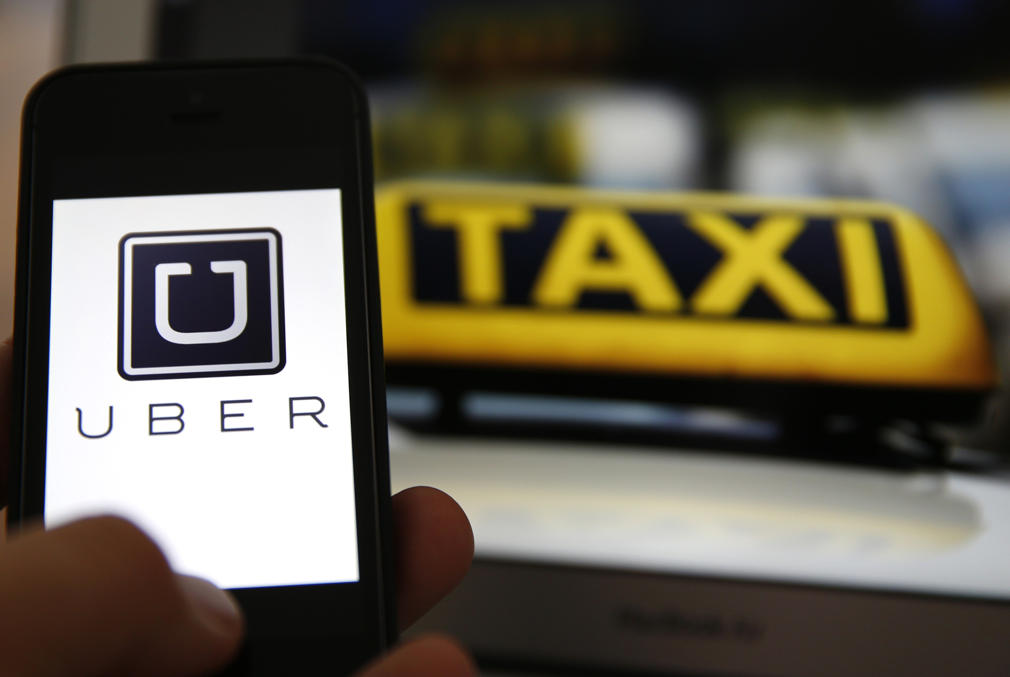 File illustration picture showing the logo of car sharing service app Uber on a smartphone next to the picture of an official German taxi sign